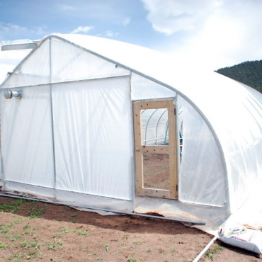 Rolling thunder greenhouse with full coverings and a fully sealed door.
